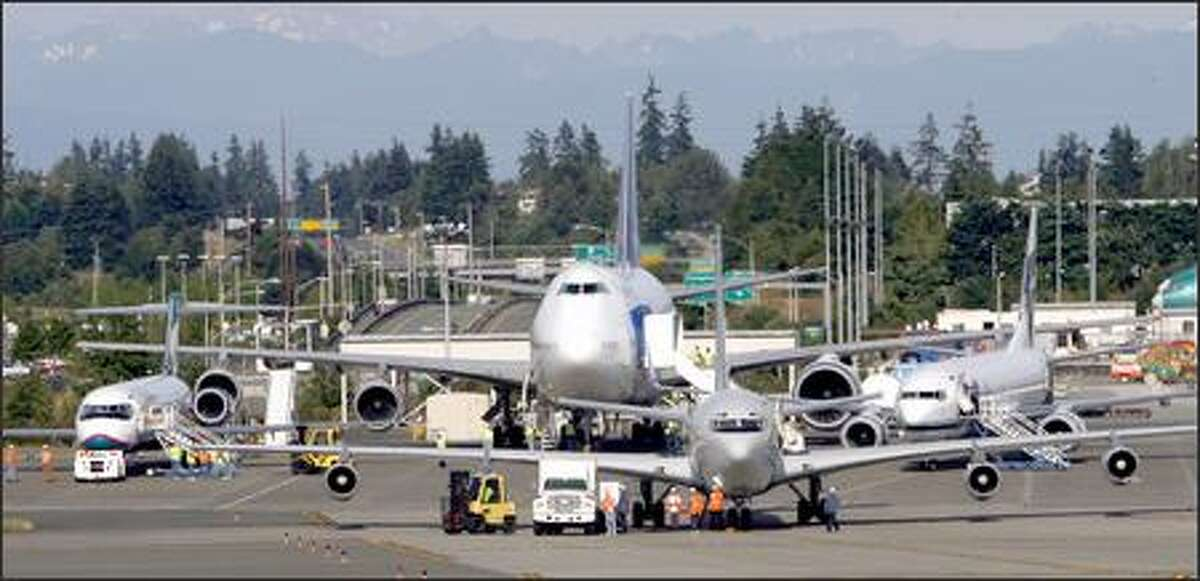 Crews get the Omega tanker 707 ready as from left, the 717, 747 and 737 wait at Boeing's Everett plant.