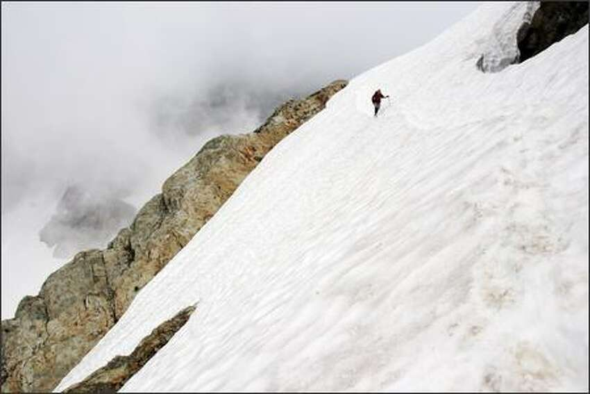 P-I reporter Greg Johnston crosses a steep exposure on the Queest-Alb Glacier during the return trip from the Three Fingers lookout in the Glacier Peak area.