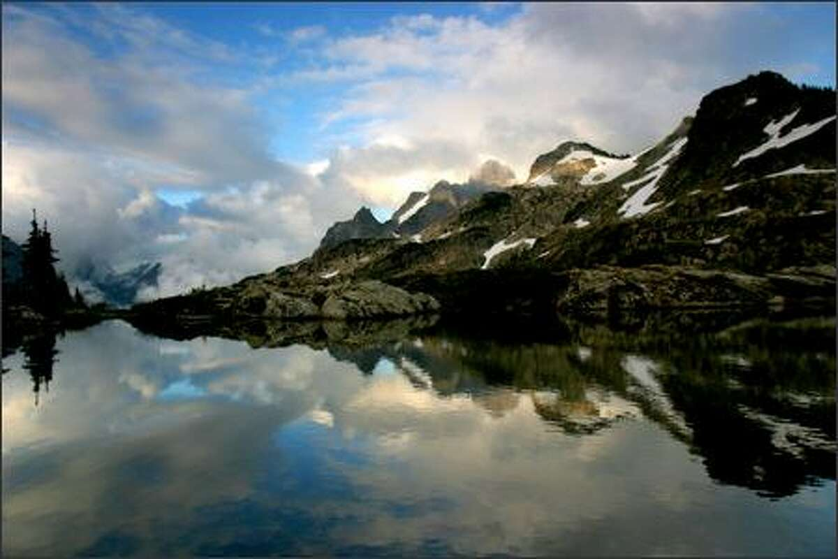 Three Fingers reflects in a tarn at Goat Flats in the Glacier Peak area.