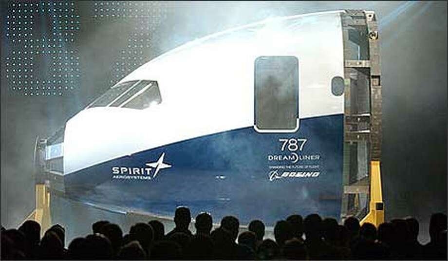 Spirit AeroSystems employees look over the first Boeing 787 Dream Liner all-composit developmental nose section after its rollout, complete with fireworks and smoke machines, in the Spirit AeroSystems plant in Wichita, Kan., Thursday. The composit manufacturing process for the all-new jetliner is considered to be the company's first major milestone since becoming a separate entity from the Wichita Boeing Commercial Aircraft Division earlier this year. (AP Photo/The Wichita Eagle, Mike Hutmacher.) Photo: / Associated Press
