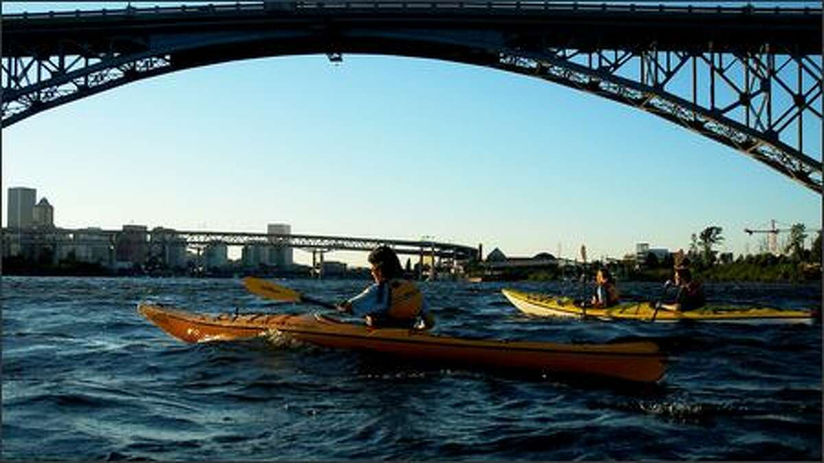 Kathy Dudek of West Linn, Ore., left, and Tina and Peter Auerbach of Portland cross under the Ross Island Bridge on the Willamette River heading back toward downtown Portland during a kayak trip on July 9, 2007.