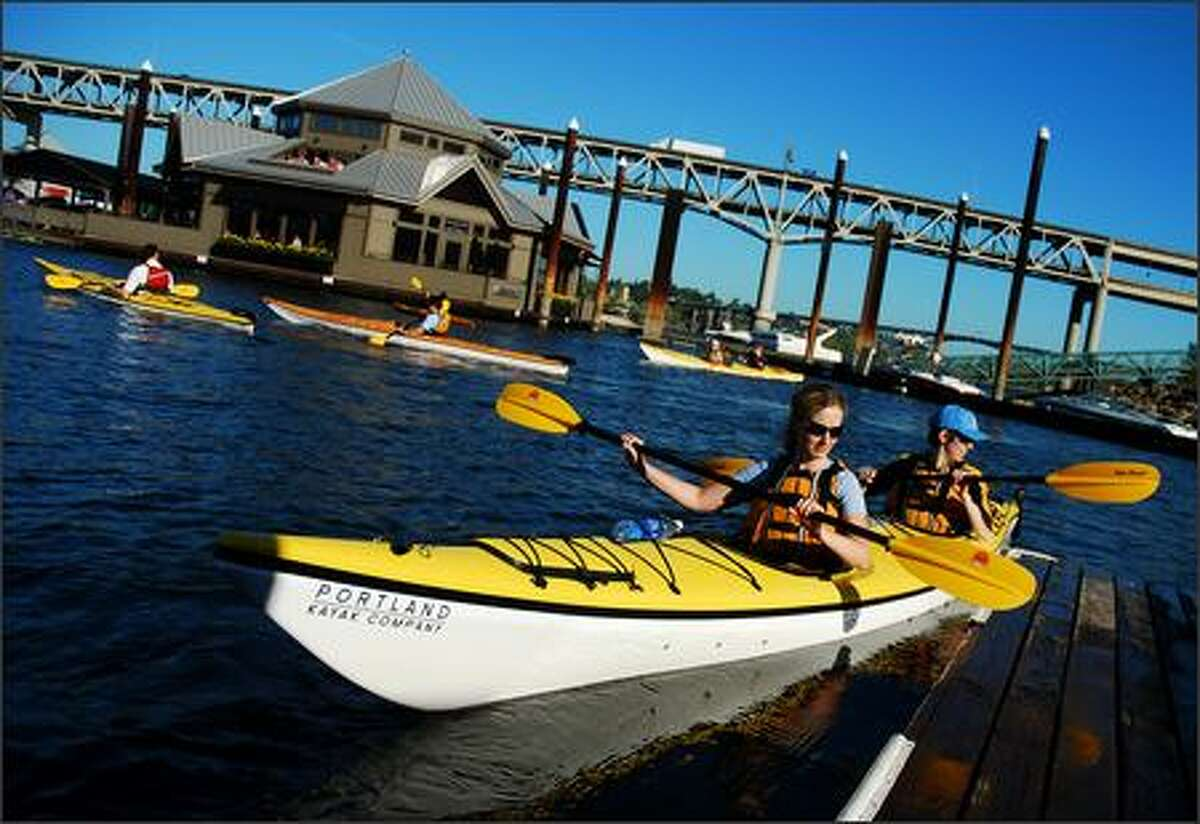 Carrie Barrett of Madison, Wis., and Allison Titus of Portland push away from the dock at the Portland Marina on the Willamette River during a kayak trip on July 9, 2007.