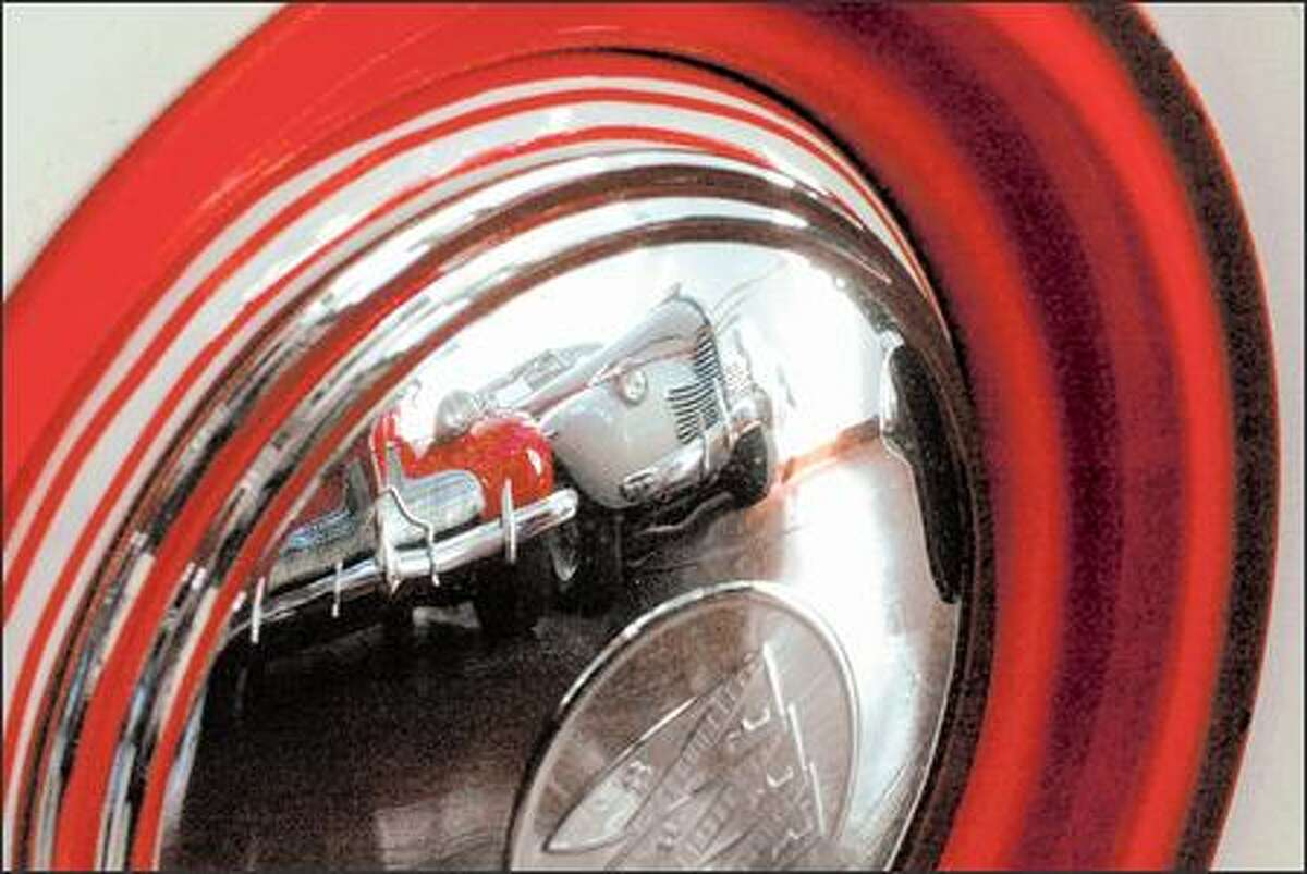 Reflected in the hubcap of a 1958 Buick is a '39 Buick Century Straight 8, left, and a '40 Buick Roadmaster.