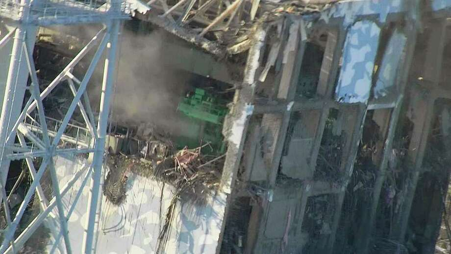 In this photo taken on Wednesday afternoon, March 16, 2011 and released on Thursday, March 17 by Tokyo Electric Power Co. (TEPCO), the top part of the badly damaged No. 4 unit of the Fukushima Dai-ichi nuclear power plant in Okumamachi, Fukushima Prefecture, is shown. A nearly completed new power line could restore cooling systems in Japan's tsunami-crippled nuclear power plant, its operator said Thursday, raising some hope of easing the crisis that has threatened a meltdown and already spawned dangerous radiation surges. (AP Photo/Tokyo Electric Power Co.) EDITORIAL USE ONLY, NO SALES