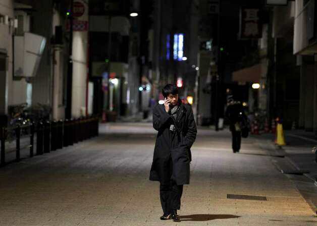 A man walks down a nearly empty street Thursday, March 17, 2011, in Tokyo. In elsewhere in the nation's capital, public apprehension over a brewing nuclear disaster is draining the streets and stores of the crowds that normally define this dynamic, densely packed city. (AP Photo/Gregory Bull) Photo: Gregory Bull
