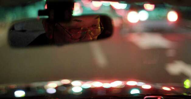 A taxi driver moves along a quiet street in Tokyo Thursday, March 17, 2011. In elsewhere in the nation's capital, public apprehension over a brewing nuclear disaster is draining the streets and stores of the crowds that normally define this dynamic, densely packed city. (AP Photo/Gregory Bull) Photo: Gregory Bull