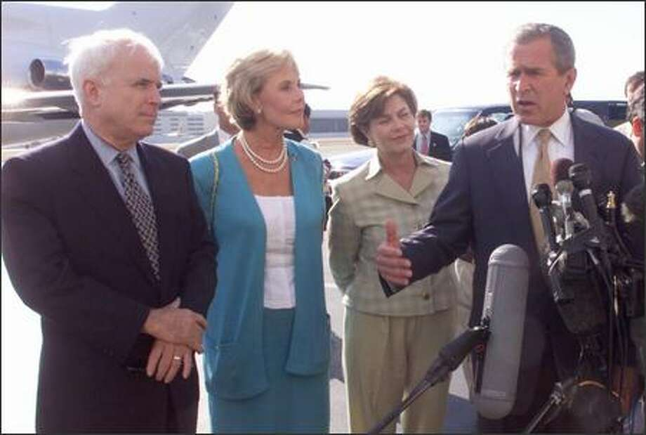 At King County International Airport on Aug. 11, 2000, Texas Gov. George W. Bush responds to a question from the press on what he would do about the decline of salmon in the Columbia and Snake rivers if he wouldn't tear down the dams. From the left, listening are Sen. John McCain, Rep. Jennifer Dunn and Mrs. Laura Bush. Photo: P-I File