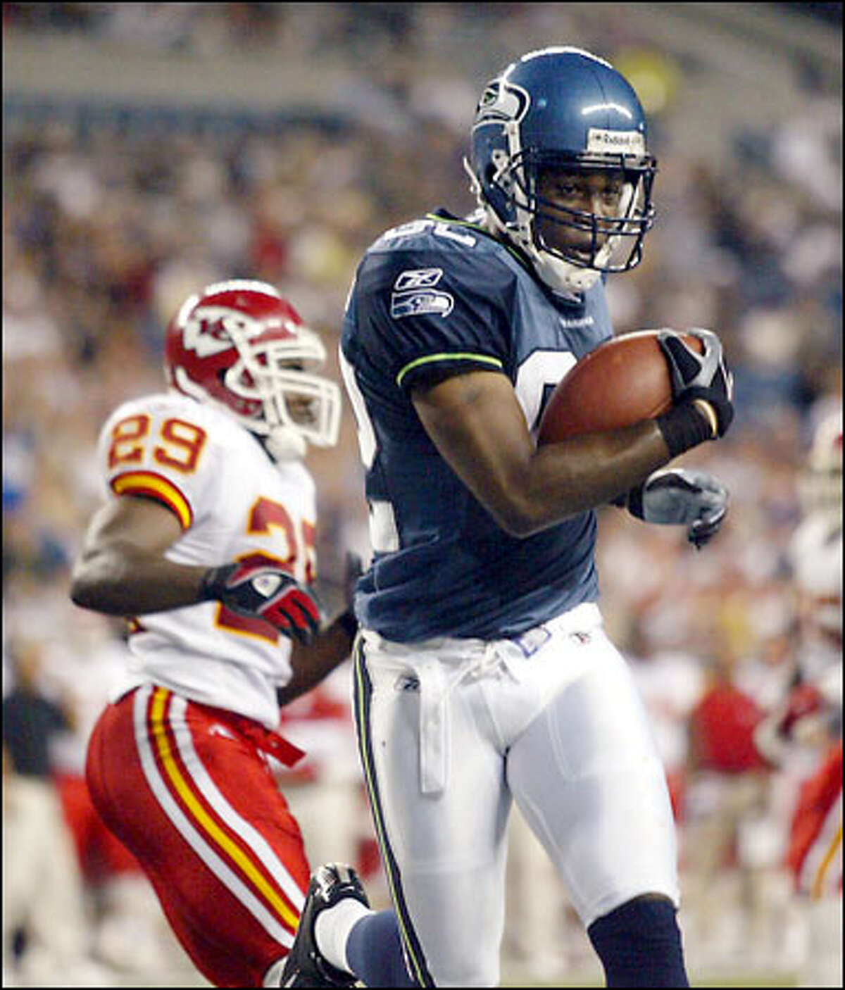 Seattle's Darrell Jackson scores on an 8-yard pass from quarterback Matt Hasselbeck, as Kansas City Chiefs defender Jason Belser runs in the background during the second quarter.