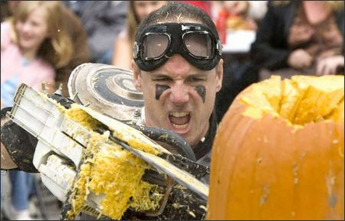 The Pumpkin Warrior, also known as Mike Christensen of Seattle, competes in the Texas Chainsaw Carving Competition.