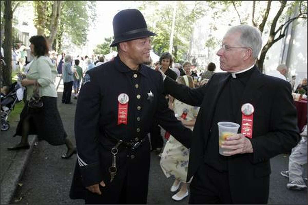 The Very Reverend Michael Ryan, the Pastor of St. James Cathedral, visits Seattle police officer Kevin Smith at a party along Terry Ave. celebrating the centenial of St. James Cathedral. The officers were wearing authentic 100-year-old uniforms for the occasion.