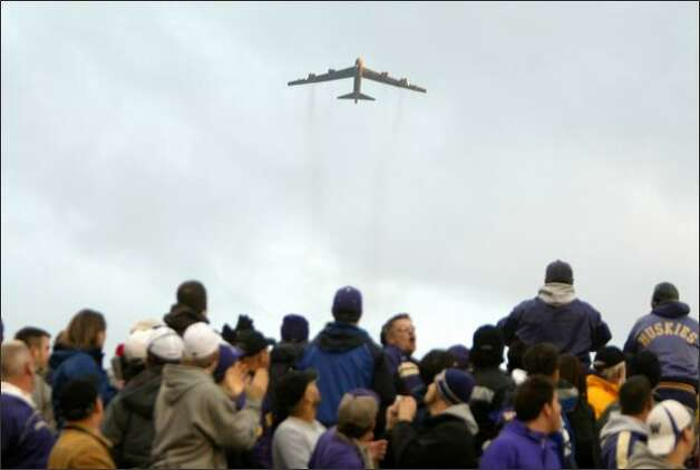 A B-52 bomber flies overhead before the start of the 2007 Apple Cup, the annual football game between  the University of Washington and Washington State University. Photo: Mike Kane, Seattle  Post-Intelligencer / SL