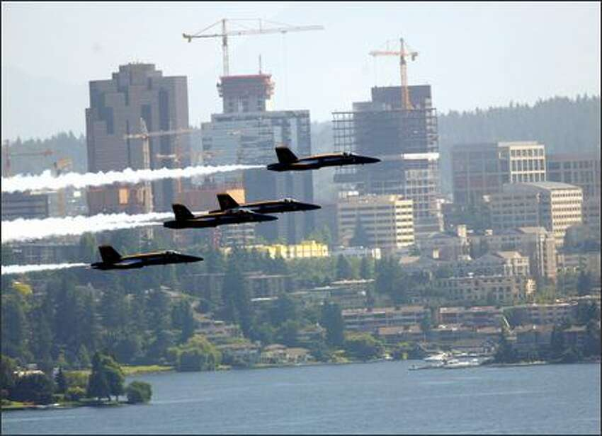 The Blue Angels fly past the downtown Bellevue skyline, as seen from the vicinity of 32nd Avenue South and South Judkins Street in Seattle.