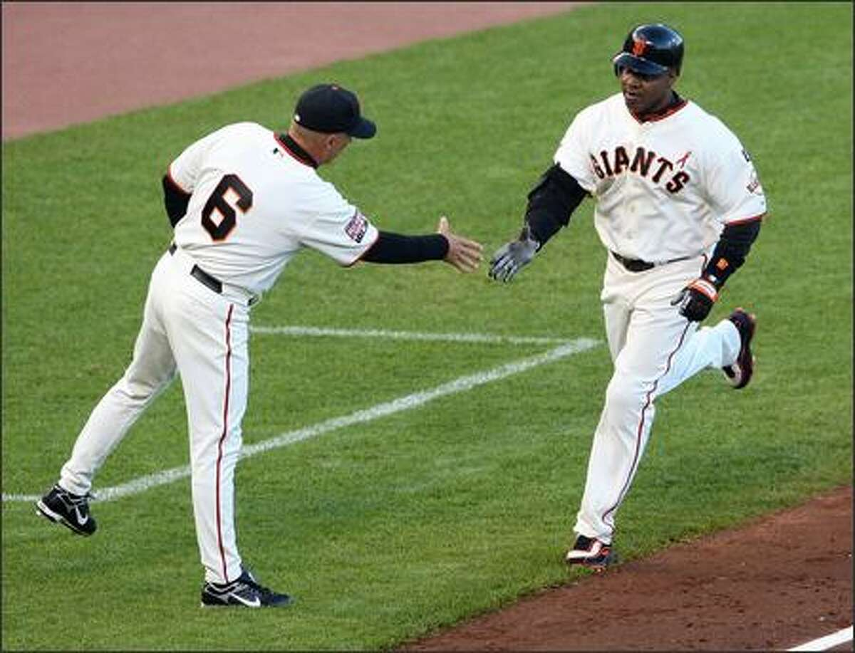 Barry Bonds #25 of the San Francisco Giants is congratulated by Tim Flannery #6 as he rounds the bases after hitting career home run number 754 during the first inning against the Florida Marlins at AT&T Park July 27, 2007 in San Francisco, California. Photo by Justin Sullivan/Getty Images