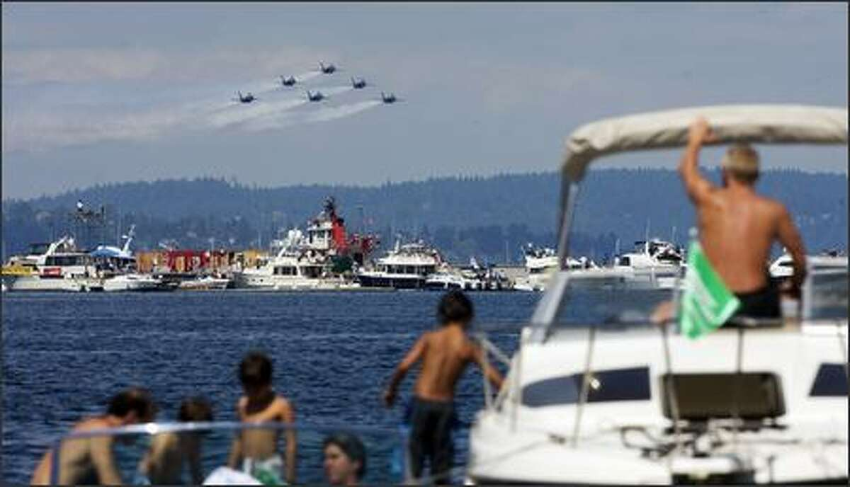 The Blue Angels fly along the boats parked at the log boom for hydro racing on Lake Washington.