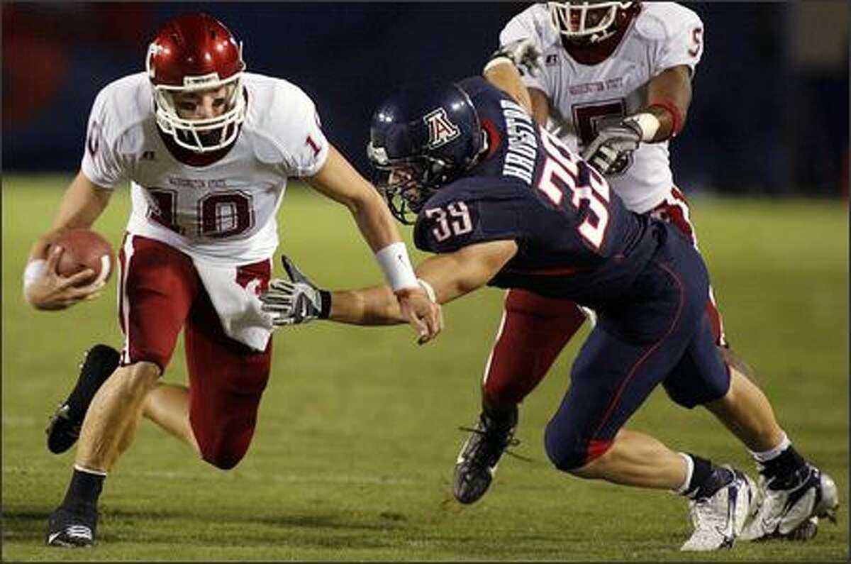 Washington State's Alex Brink (10) is dragged down on a quarterback keeper by Arizona's Dane Krogstad (39) during the second quarter. (AP Photo/John Miller)