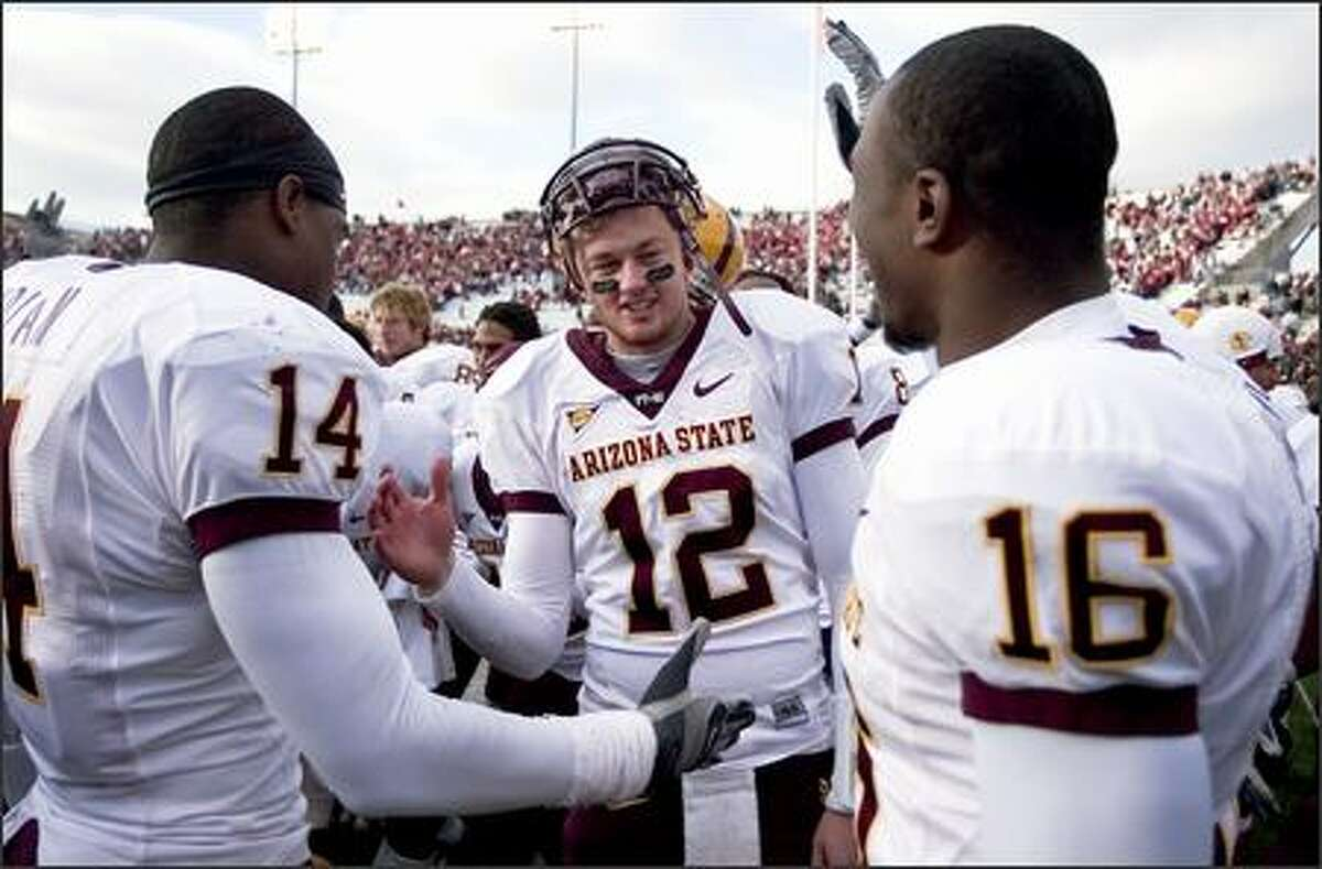 Quarterback Rudy Carpenter (12) is congratulated by teammates Troy Nolan (14) and Nate Kimbrough (16) after Arizona State defeated Washington State, 23-20. (AP Photo/Dean Hare)