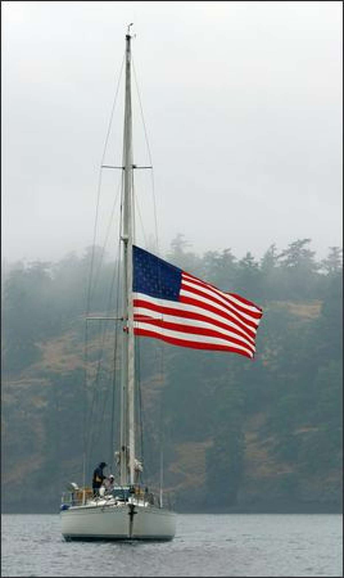 A sailboat flying the Stars and Stripes passes Spieden Island in the San Juan Islands.