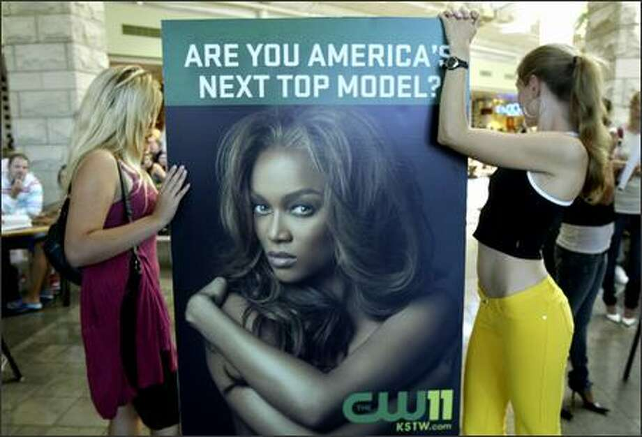 "Applicants Ekaterina Thormann, left, and Olya Valdez pose with a poster for ""America's Next Top Model,"" featuring its host and creator, former supermodel Tyra Banks. The hit reality television show airs on the CW Network (channel 11 in the Seattle area). Photo: Andy Rogers, Seattle Post-Intelligencer"
