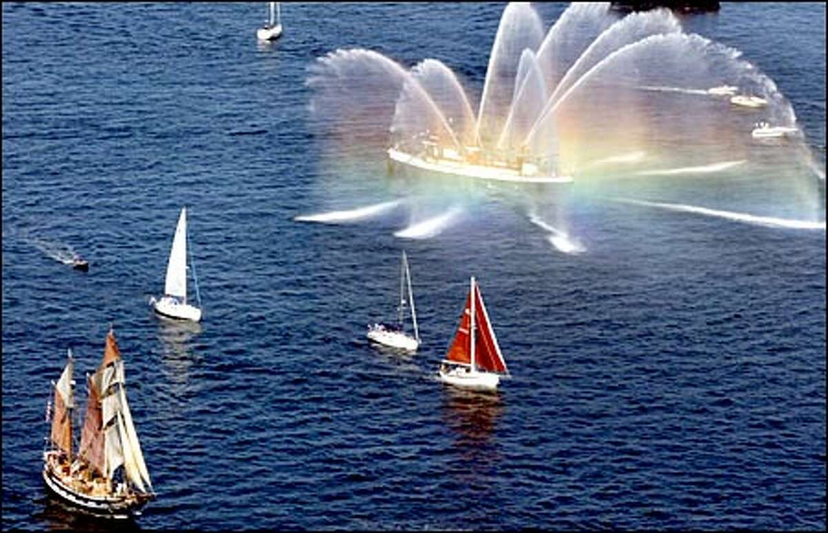 The Hawaiian Chieftain, a square topsail ketch, left, is greeted by the Alki fire boat as a rainbow reflects off the water in Elliott Bay.