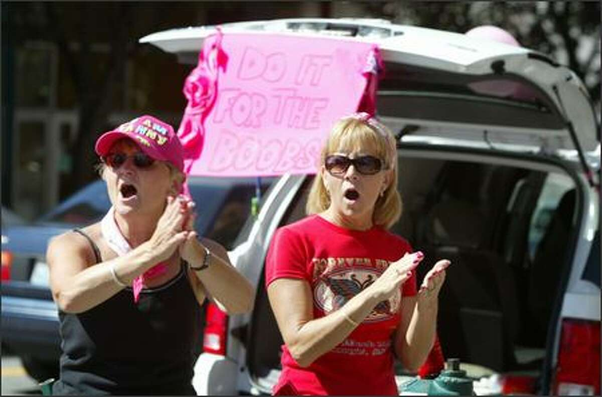 Linda Osterholt and Karen Baker cheer on participants on the final day of the Seattle Breast Cancer 3-Day fund raiser.
