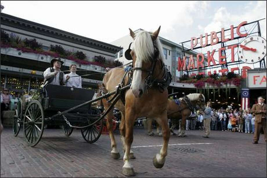 Wayne Buckner and Susanna Burney park Holly, a Belgian horse, carrying produce, at the Market at Pike Place and 1st Ave., in a re-enactment of August 17, 1907, the Market's first day of operation. Photo: Meryl Schenker, Seattle Post-Intelligencer