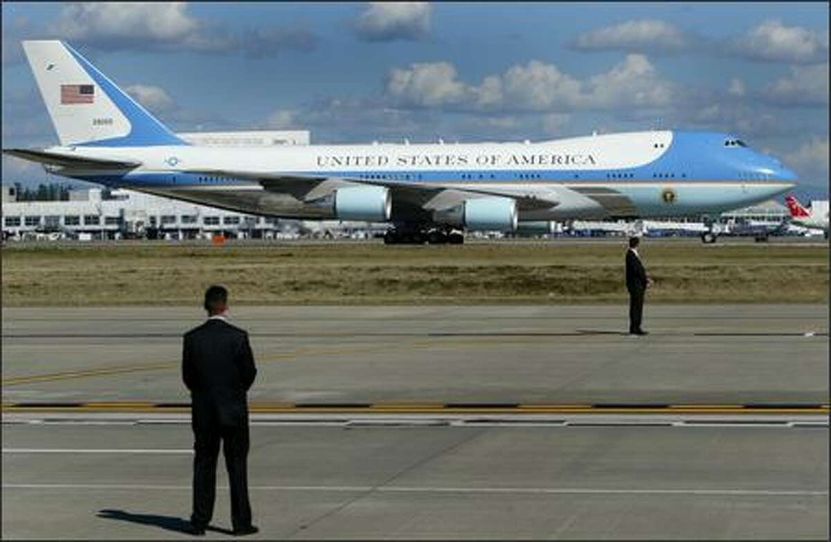 An advance team waits as U.S. President George W. Bush and Air Force One taxi at SeaTac Airport on Monday, August 27, 2007 during a brief trip to the area to raise funds for Congressman Dave Reichert and the Republican Party. Story: Bush says Reichert 'tough,' 'compassionate'
