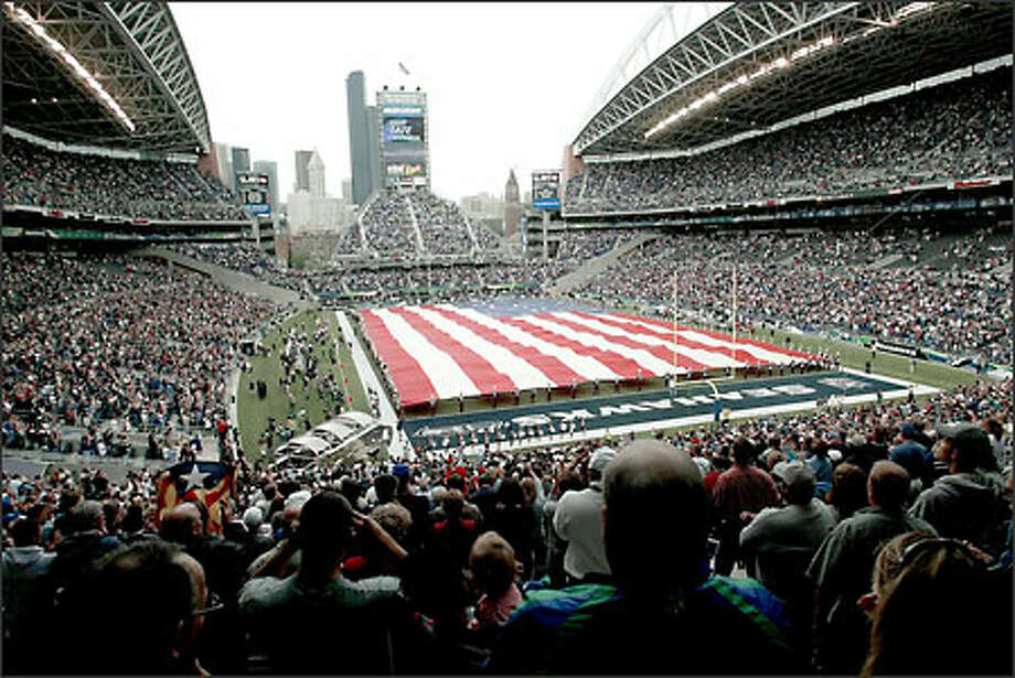 The U.S. flag covers the floor of the Seahawks Stadium during the National Anthem. Photo: Paul Kitagaki Jr., Seattle Post-Intelligencer