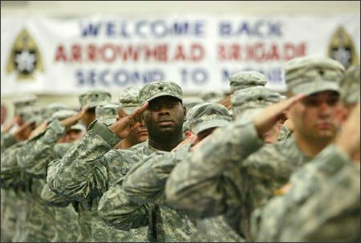 Members of the Stryker Brigade salute during the playing of the National Anthem as they return to Fort Lewis.