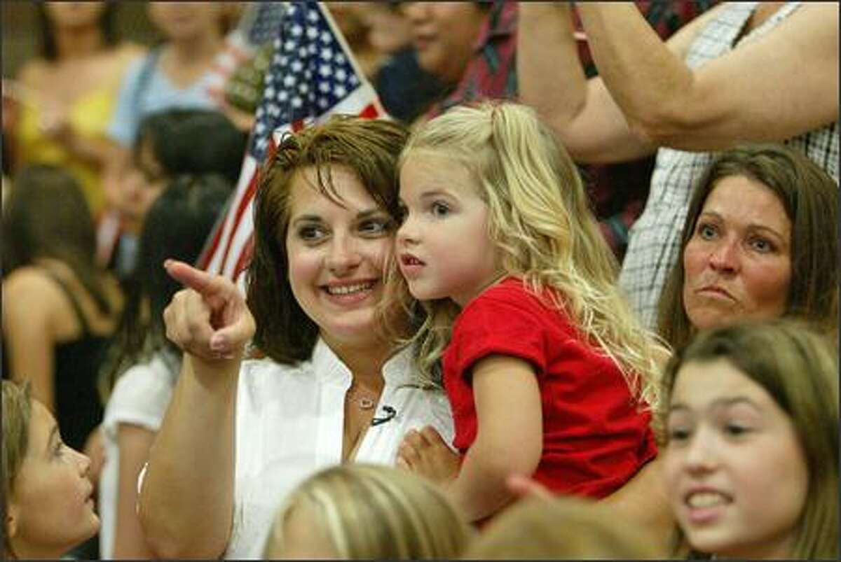 Rebecca Trythall points out daddy (Joshua Trythall) to daughter Madison as members of the Stryker Brigade return to Fort Lewis.