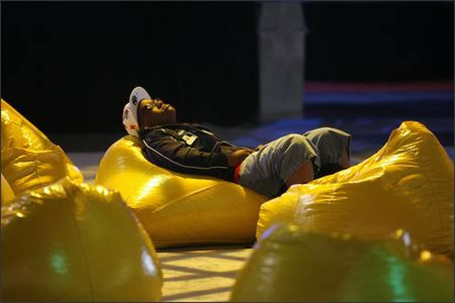 Jeremy Florence, of the USA team, prepares for his late afternoon battle in Dead or Alive 4 by lying in a beanbag and listening to music in a central gathering area. Photo: Grant M. Haller, Seattle Post-Intelligencer