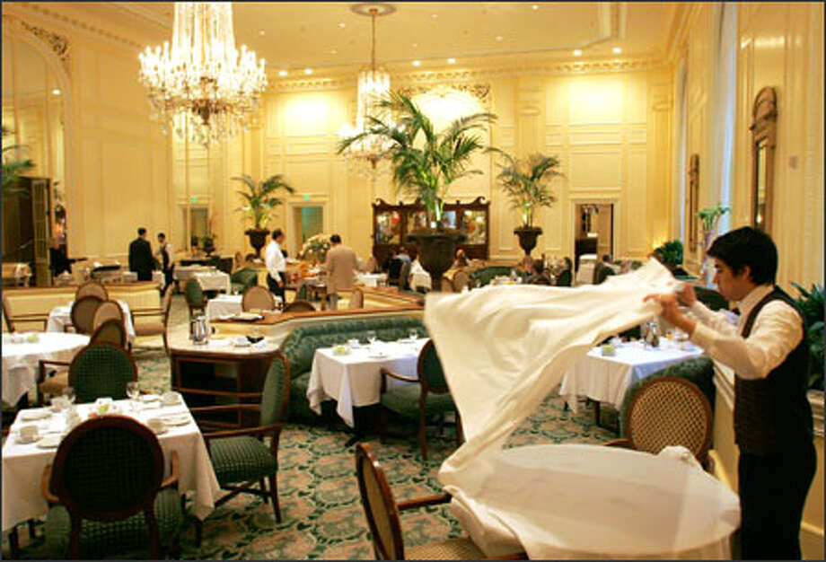 Juan Jimez sets a table in the elegant Georgian Room at The Fairmont Olympic Hotel in downtown Seattle. The room has retained much of its design -- and the original chandeliers -- from the hotel's opening in 1924. The Georgian Room is open for breakfast, lunch, afternoon tea and dinner. Photo: Niki Desautels/Seattle Post-Intelligencer / SEATTLE POST-INTELLIGENCER
