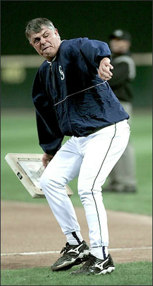 """Mariners manager Lou Piniella throws first base in a fit of utter rage during a game against Texas on Sept. 18 at Safeco Field. Piniella went nuts after a bad call and an ensuing """"smirk"""" from the first-base umpire. Photo: Dan DeLong, Seattle Post-Intelligencer"""