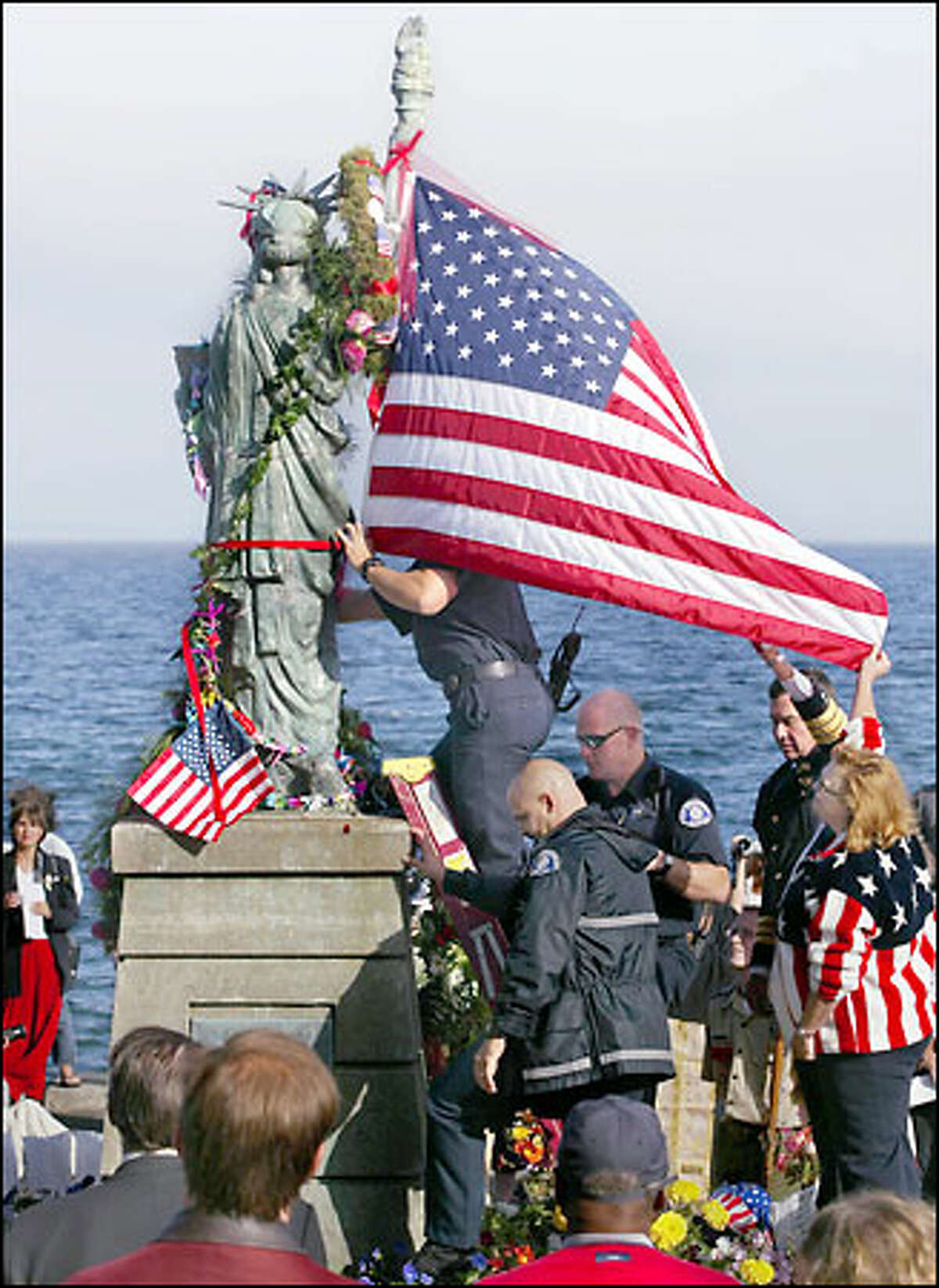 Cindi Laws, bottom right, returned to Alki, where she sought solace last Sept. 11, to place an American flag on the Statue of Liberty. Assisting were Seattle police Chief Gil Kerlikowske, behind her, Seattle firefighters Jason De Bruler, top, Roland Falb, in glasses, and L.T. Grant.