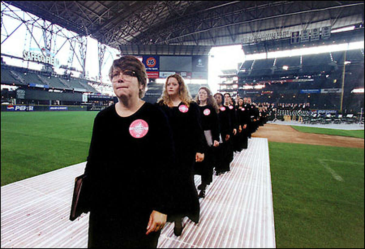 Members of Seattle Symphony Chorale file off the diamond at Safeco Field after performing in the Emerald City's installment of the Rolling Requiem, in which some 180 groups from 26 countries performed Mozart's Requiem in commemoration of the events of Sept. 11, 2001.