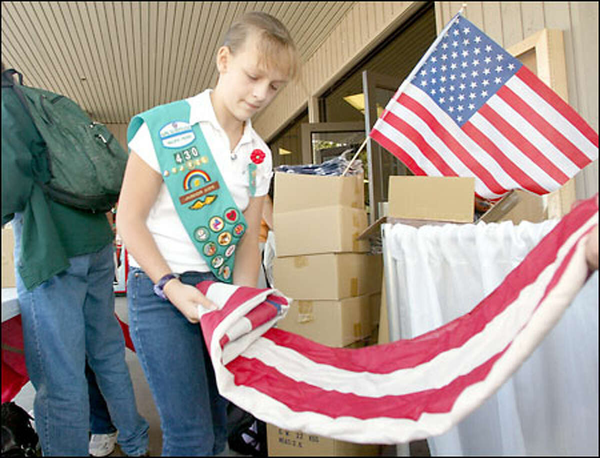 Girl Scout Maggie Roger, 11, folds a used flag that a visitor exchanged for a new one at the Puyallup Fair. About 500 old flags were turned in for new ones.