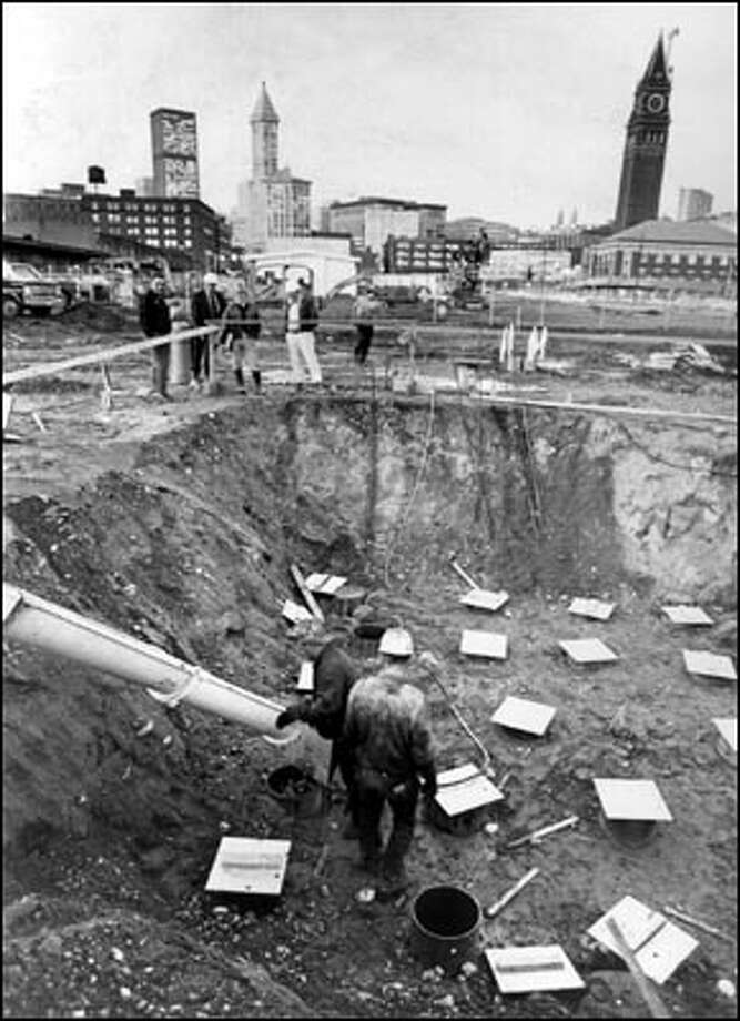 July 10, 1972:  Workmen begin pouring concrete for the foundations of King County's new domed stadium.  This angle looks northeast; the steepled roof of historic Smith Tower juts skyward from the horizon at left and Union Station's clock tower juts skyward on the right. Photo: Seattle Post-Intelligencer