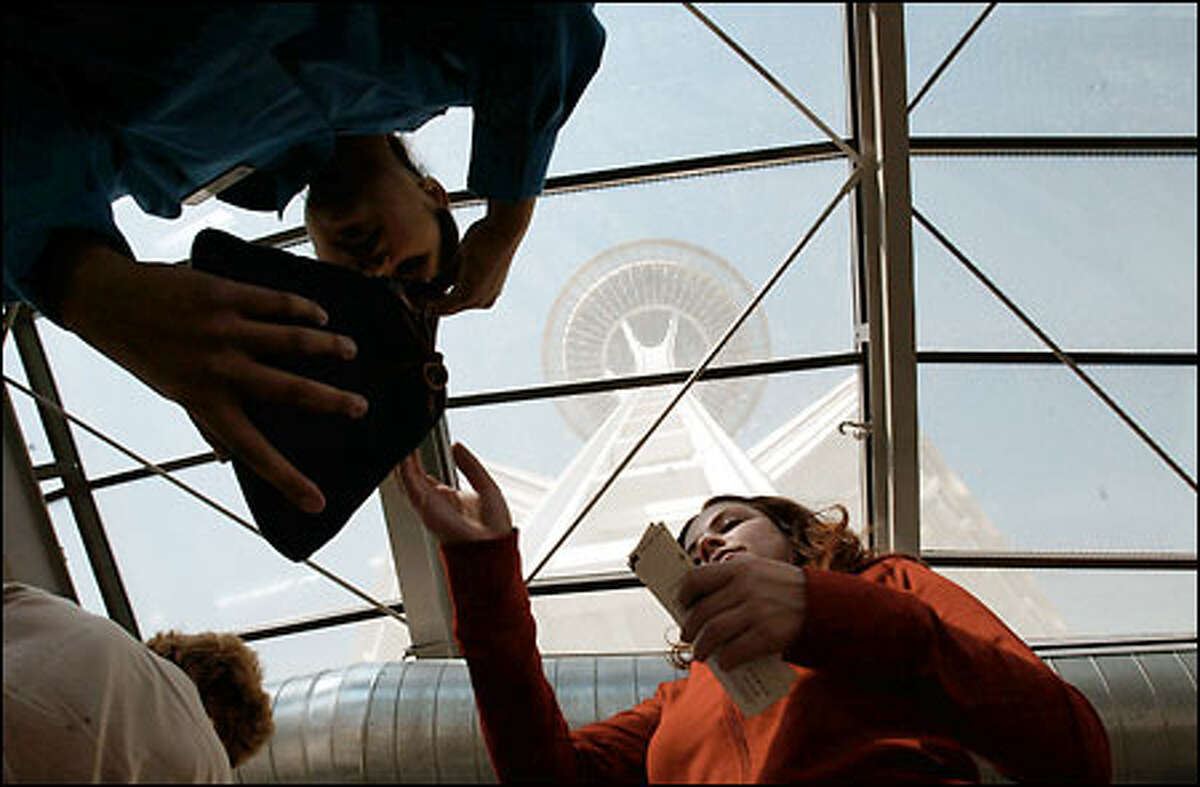 Security employee Tokyo Phengphachanh, upper left, checks visitors' bags at the Space Needle.
