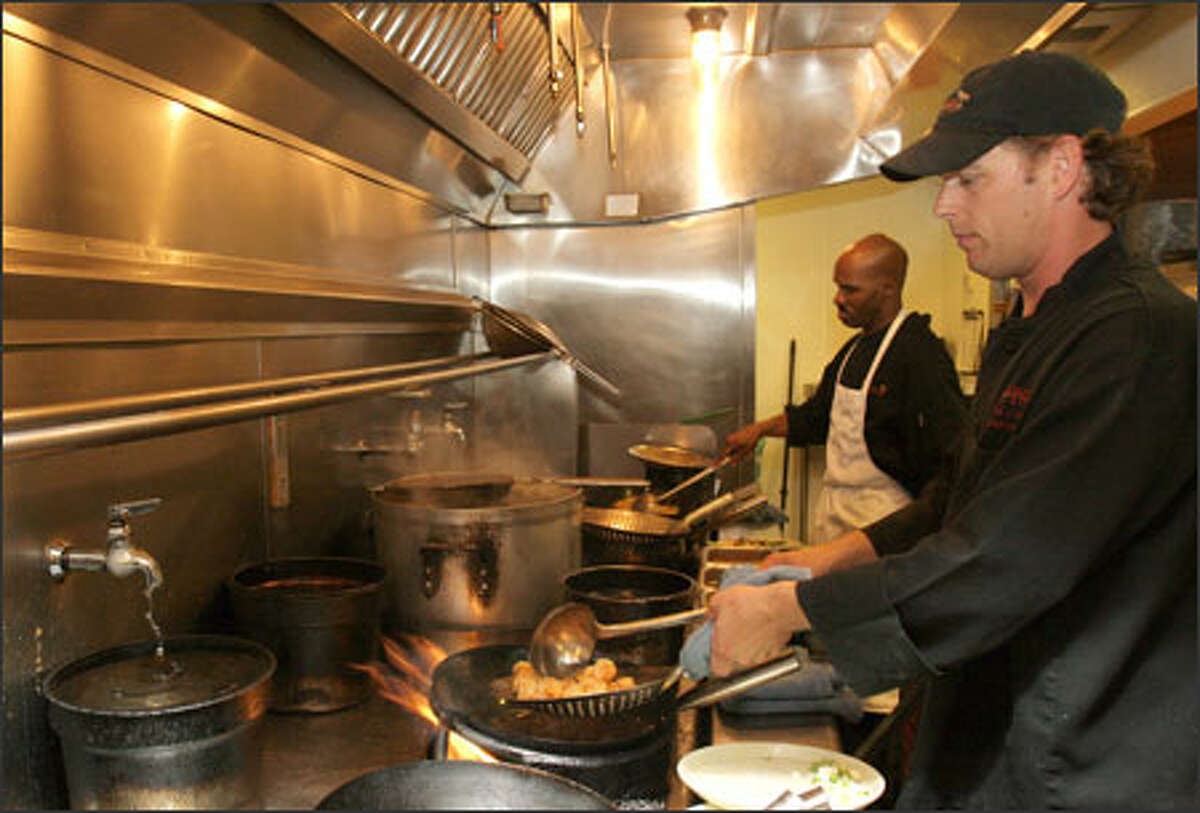 Chef David Cochran prepares spicy shrimp, one of the gluten-free dishes available at P.F. Chang's China Bistro in Seattle.