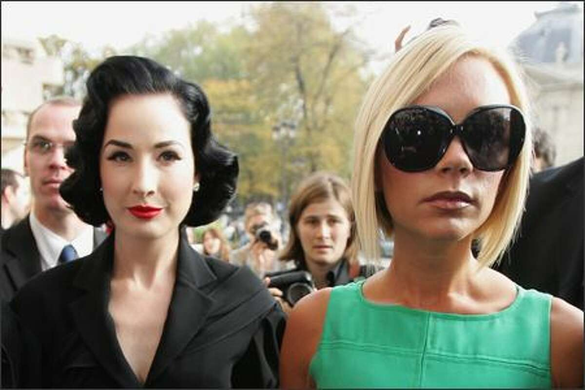 Singer Victoria Beckham (R) and burlesque artist Dita Von Teese (L) arrive to attend the Chanel Fashion show during the Paris Fashion Week Sp/Sum October 5, 2007 in Paris, France.