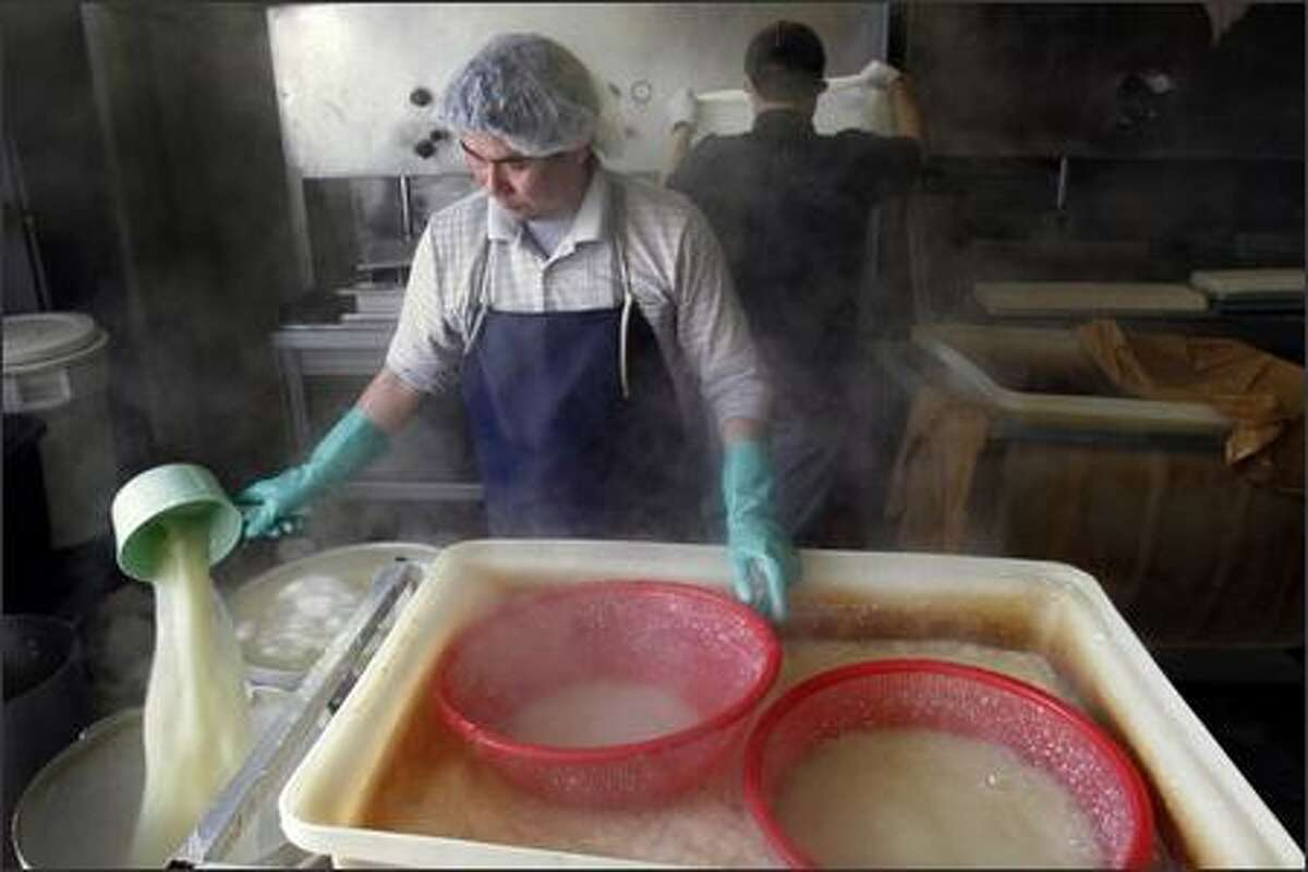 Luong Ho removes the whey from the coagulant (soybean curd) before it is placed into molds and pressed.