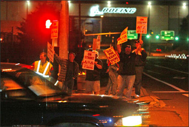 Boeing Machinists wave picket signs and yell at workers leaving the company's Everett plant early Friday morning. Photo: Grant M. Haller/Seattle Post-Intelligencer