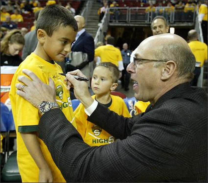 Sonics radio announcer Kevin Calabro autographs 8-year-old Robby Proano's shirt under the watchful eye of brother Michael, 6, prior to the home opener against the Phoenix Suns.