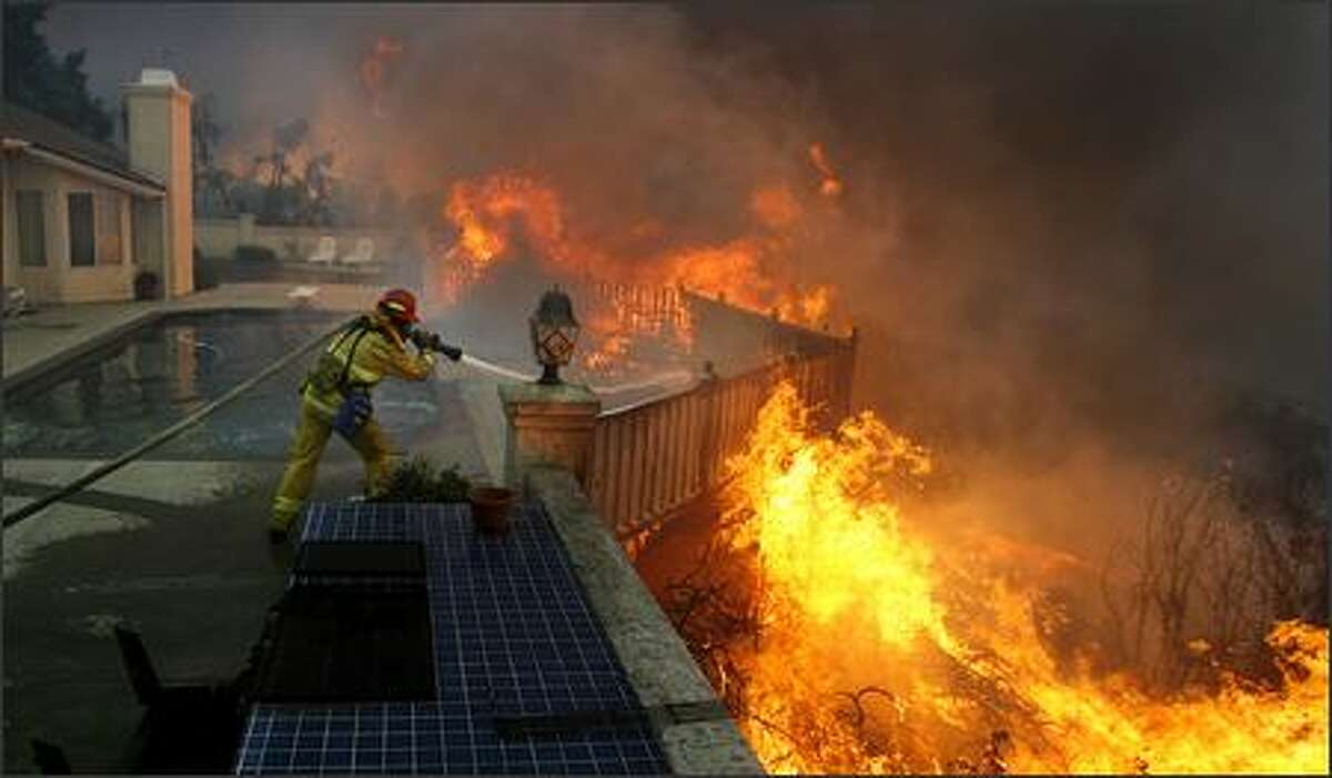 Firefighter Jason Falarski battles to save a house on Sand Hill Road, in Poway, Calif.