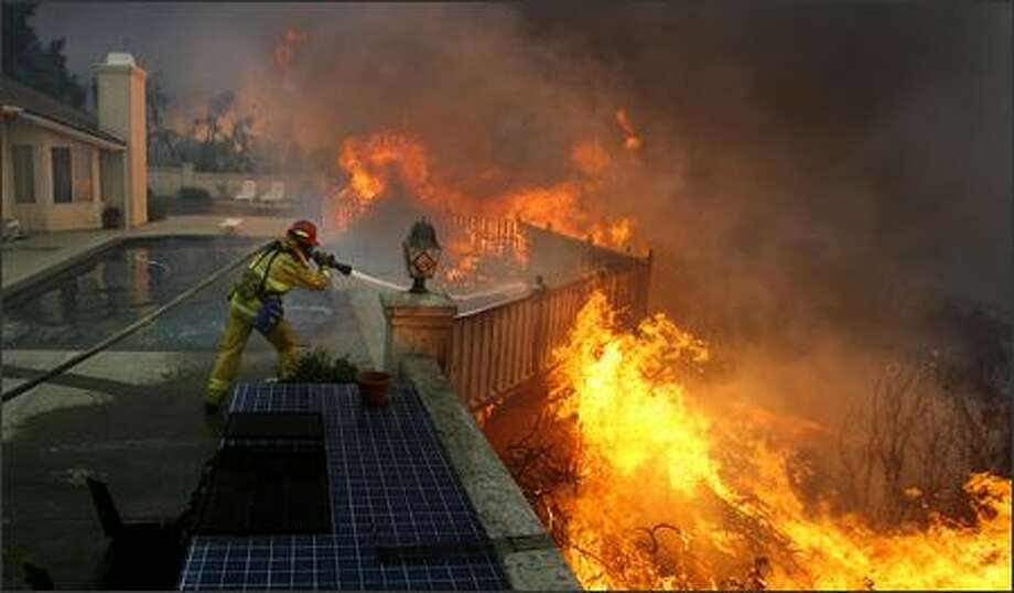 Firefighter Jason Falarski battles to save a house on Sand Hill Road, in Poway, Calif. Photo: Wally Skalij, AP Photo/Los Angeles Times
