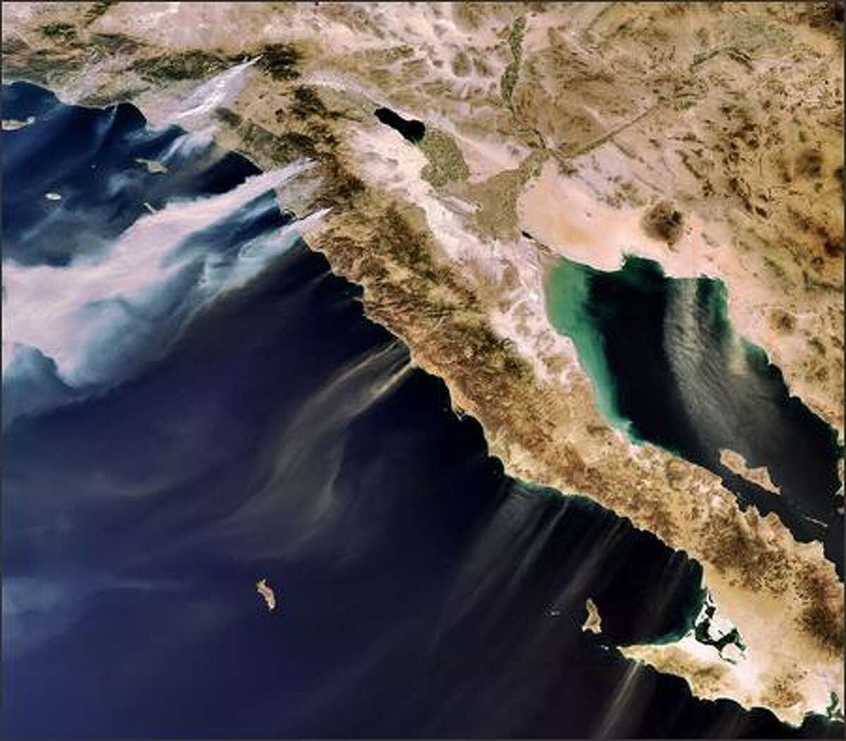 A photo provided by the European Space Agency ESA shows the Envisat's MERIS image, acquired on Oct. 22, 2007, of desert winds blowing smoke from wildfires in Southern California. Sand is visible being blown from Mexicos Baja California Peninsula over the Gulf of California to the east and the Pacific Ocean to the west.