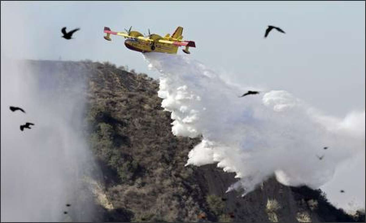 A Super Scooper drops water on a hot spot where a wildfire driven by powerful Santa Ana winds threatened homes.