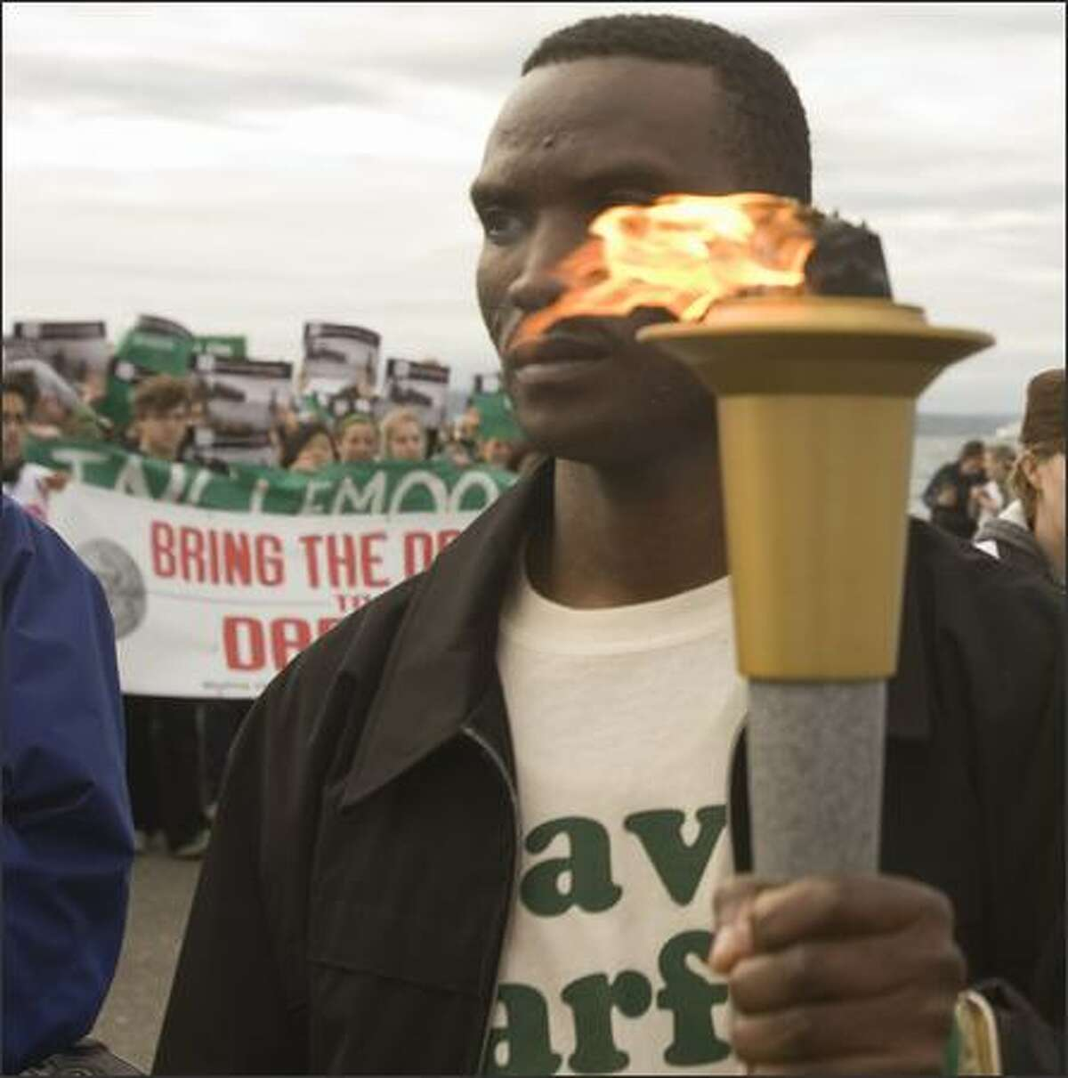 Darfur genocide survivor Ibrahim Adam carries the torch during the Seattle portion of the symbolic Dream for Darfur Olympic Torch Relay, which began in Darfur and will end in Beijing, the site of the 2008 Summer Olympics. The event is a global initiative aimed at urging China to use its considerable influence to help bring an end to the genocide in the Darfur region of Sudan.