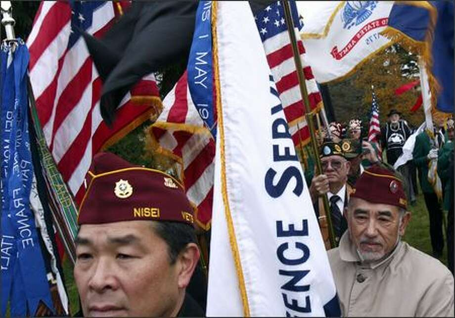 Dale Watanabe, front, and Tom Ohtani of the Nisei Veterans Committee, and Chuck Gehrts, of American Legion Post 124, wait with other veterans to take part in Parade of Colors that would begin the 58th Annual Veterans Day Service of Remembrance at Veterans Memorial Cemetery. Photo: Andy Rogers, Seattle Post-Intelligencer