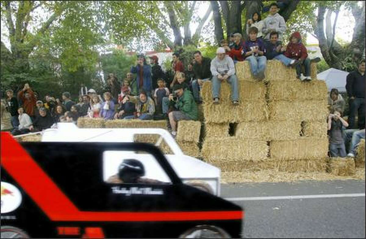 Spectators take advantage of bales of hay that line the course to get a better view of racers during the Red Bull Soapbox Race in Fremont.