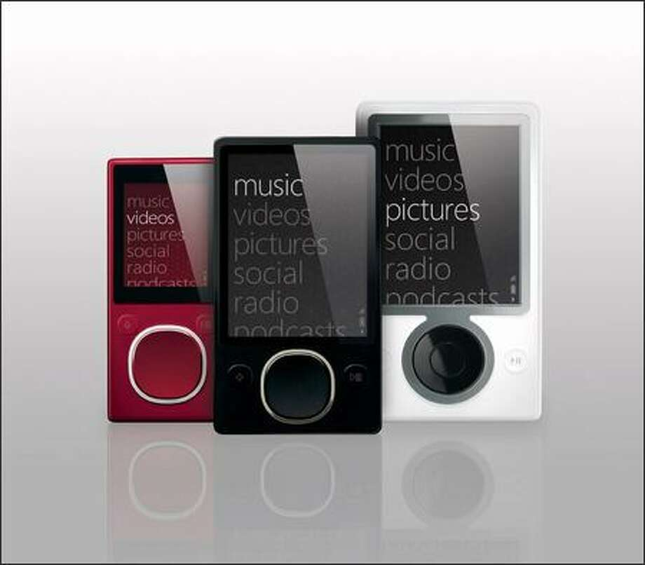 The new Zunes -- the 4 or 8 model on the left and the 80 GB version in the center -- were both noticeably smaller than the first-generation Zune, shown in white at right. Photo: Microsoft